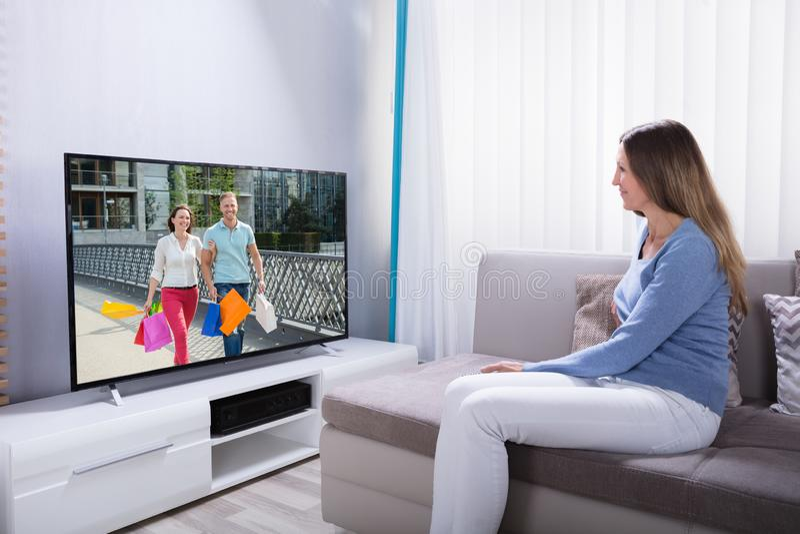 说谎在沙发观看的电视上的妇女 免版税图库摄影