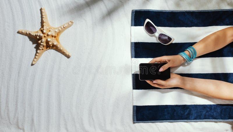 说谎在海滩和连接用她的智能手机的妇女 图库摄影
