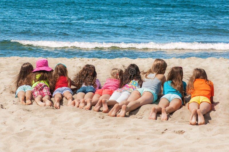 说谎在海滩的小组孩子 免版税库存图片