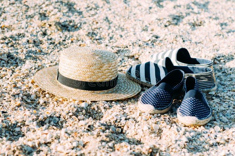 说谎在海滩的沙子的草帽和帆布鞋 背景概念框架沙子贝壳夏天 放松的假日,海滩假期 库存图片