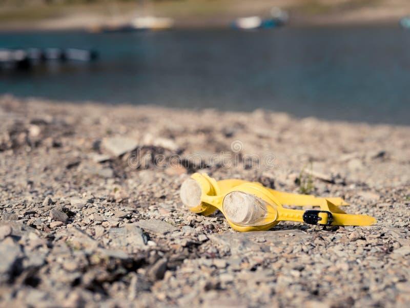 说谎在海滩的老游泳的风镜 免版税库存图片