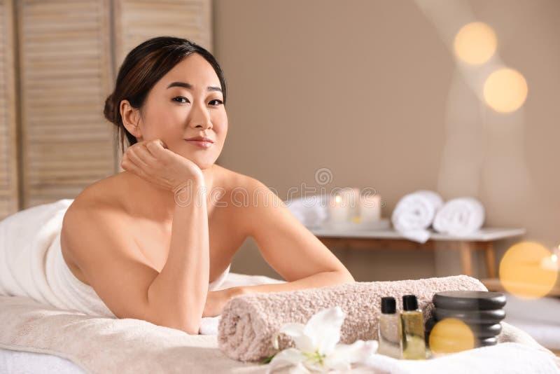 说谎在温泉沙龙的按摩桌上的美丽的亚裔妇女 免版税库存图片