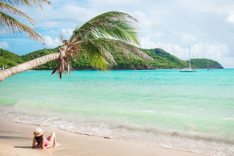 说谎在热带海滩的比基尼泳装和草帽的年轻亭亭玉立的妇女 美丽的女孩在浅水区的棕榈树下 库存照片