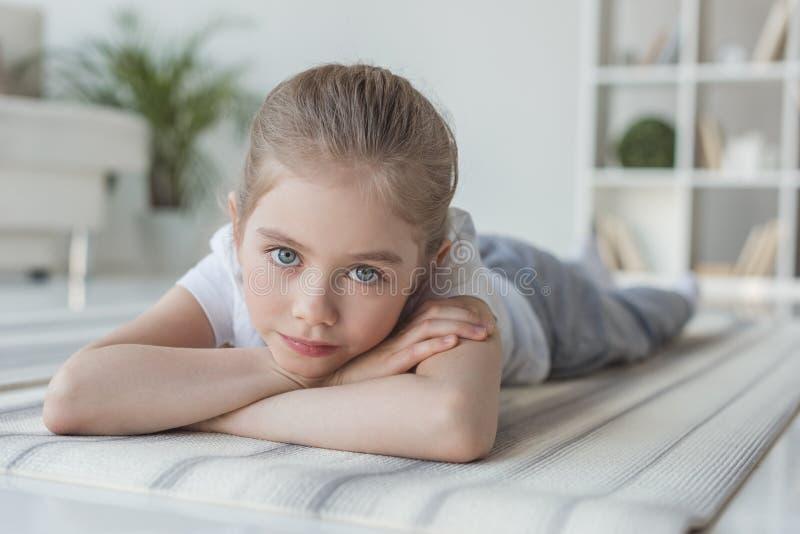 说谎在瑜伽席子和看的小孩特写镜头画象 图库摄影