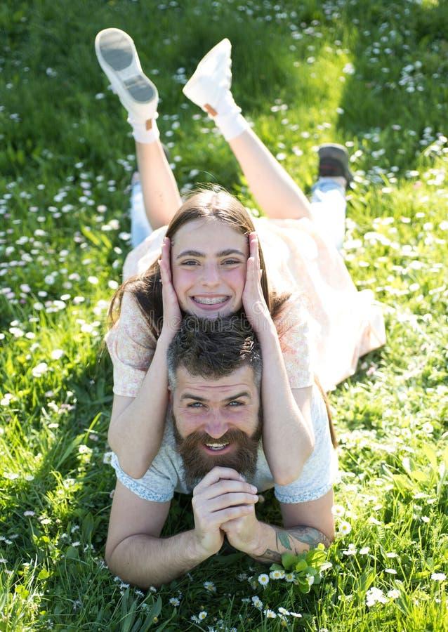 说谎在用花装饰的草甸的愉快的家庭 有胡子的人和他俏丽的深色的女儿野餐的在乡下 可爱 图库摄影