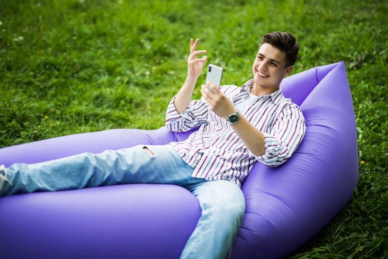 说谎在电话的可膨胀的沙发lamzac用途的英俊的年轻人,当基于草在公园时 图库摄影