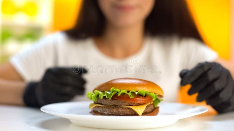 说谎在白色板材,在黑橡胶手套的女性手的肥胖双重汉堡 免版税图库摄影