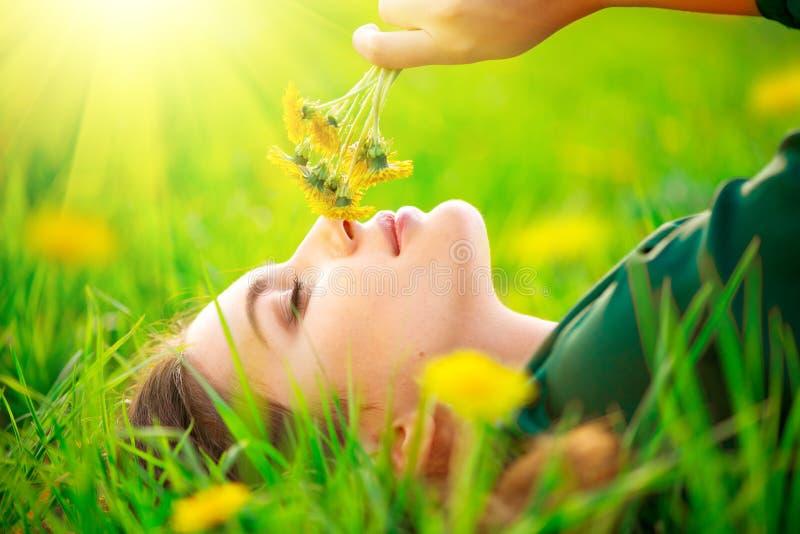 说谎在绿草和嗅到的开花的蒲公英的领域的美丽的少妇 草甸 免版税图库摄影