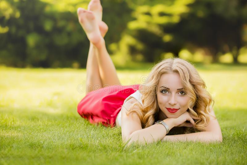说谎在绿草在公园和看照相机的有吸引力的女性模型顶视图在采取休息,画象的时刻  免版税图库摄影