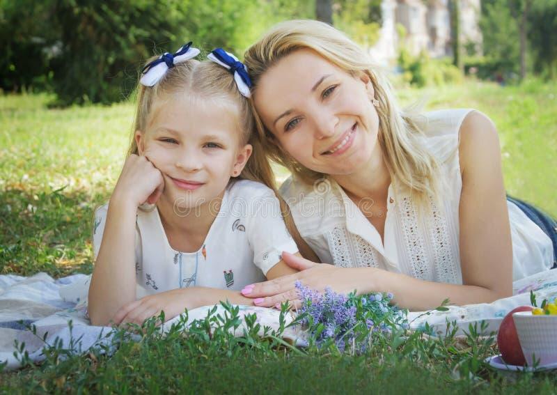 说谎在绿草的母亲和女儿 库存照片