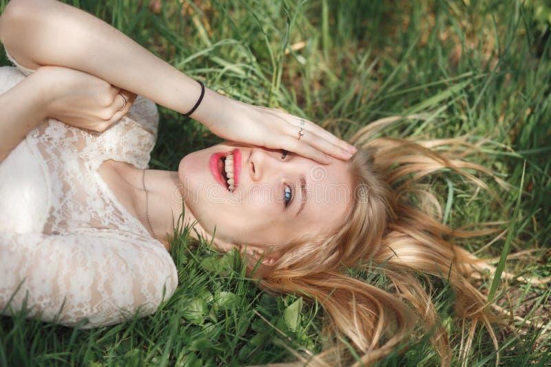 说谎在绿草的美丽的白肤金发的女孩室外画象  库存图片