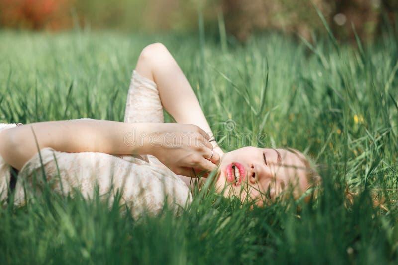 说谎在绿草的美丽的白肤金发的女孩室外画象  免版税库存照片