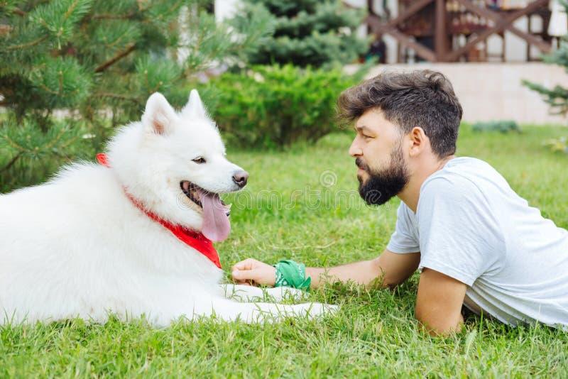 说谎在绿草的英俊的人在他的白色狗附近 免版税图库摄影