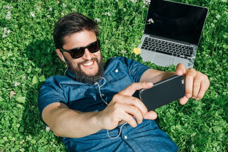 说谎在绿草的英俊的人在公园和听的musi 免版税库存照片