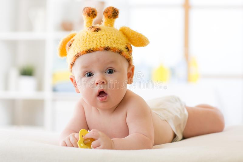 说谎在肚子和weared滑稽的长颈鹿帽子的可爱的男婴 图库摄影