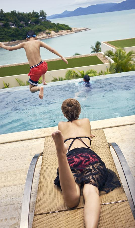 说谎在胃的亚裔妇女背面图晒日光浴在轻便折叠躺椅,当跳进水池时的孩子 免版税库存照片