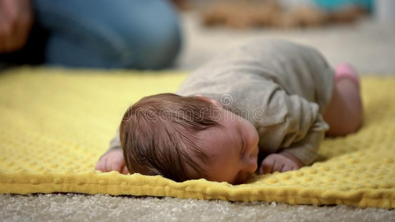 说谎在腹部的微小的可爱的婴儿女孩设法爬行,新出生的发展 库存图片