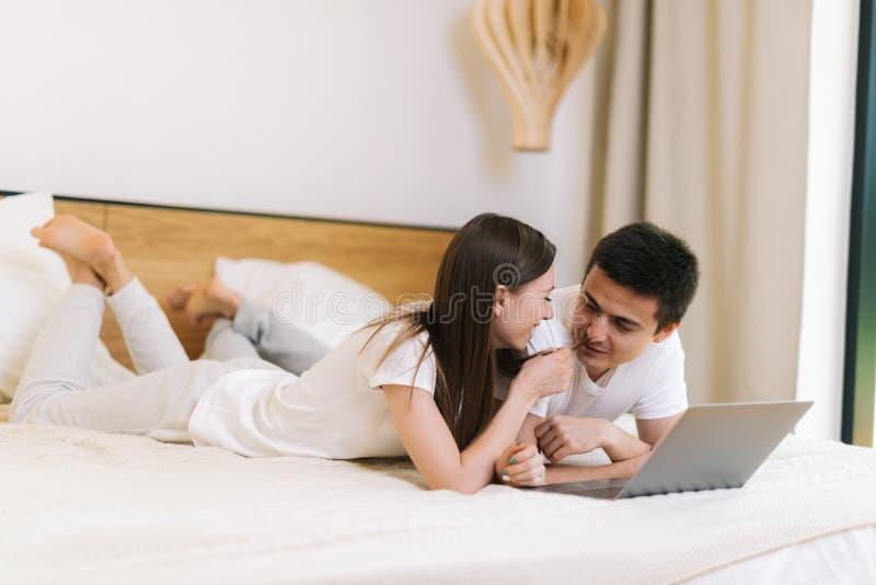 说谎在膝上型计算机前面的床上的女孩和人年轻夫妇在轻的卧室 库存照片