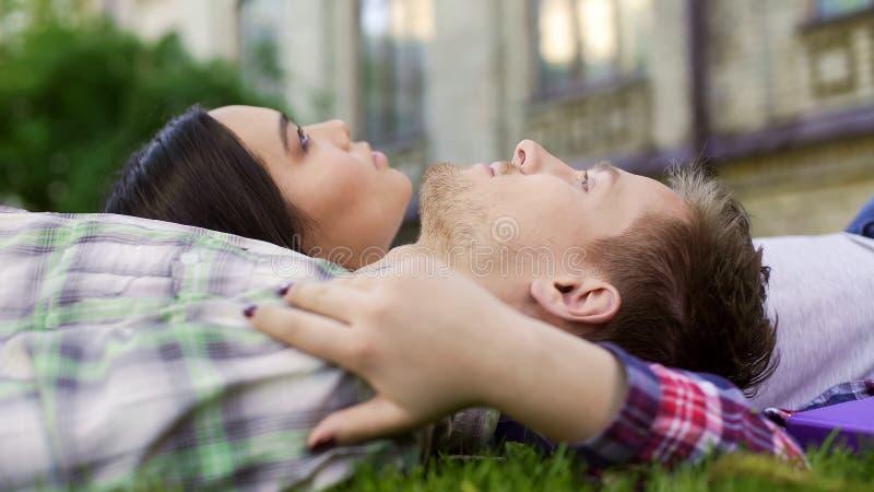 说谎在草和享有日期、爱和支持,特写镜头的沉思夫妇 库存图片