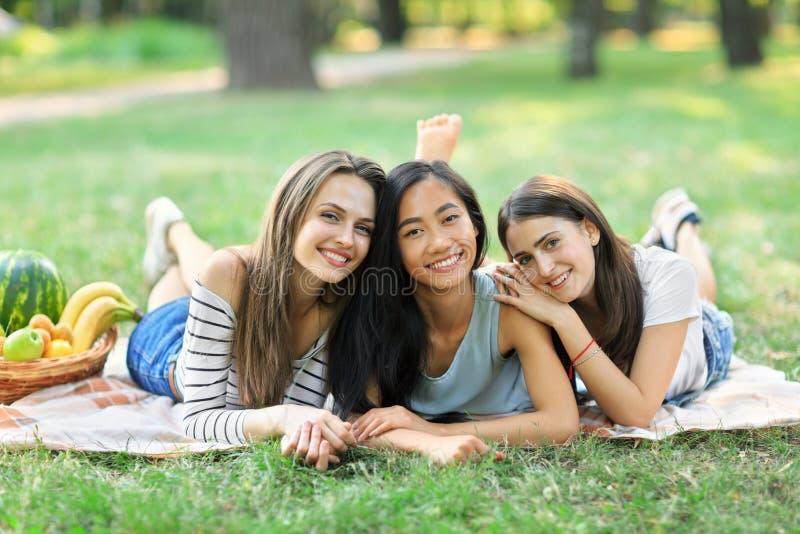 说谎在草的三名年轻愉快的多种族妇女在公园 免版税图库摄影