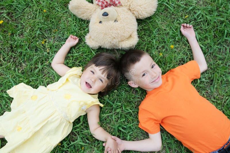 说谎在草的孩子顶视图在获得的公园乐趣 小女孩和男孩放松与微笑 玩具熊玩具 免版税库存照片