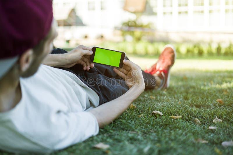 说谎在草的年轻人在城市公园使用有色度钥匙的电话 免版税库存图片