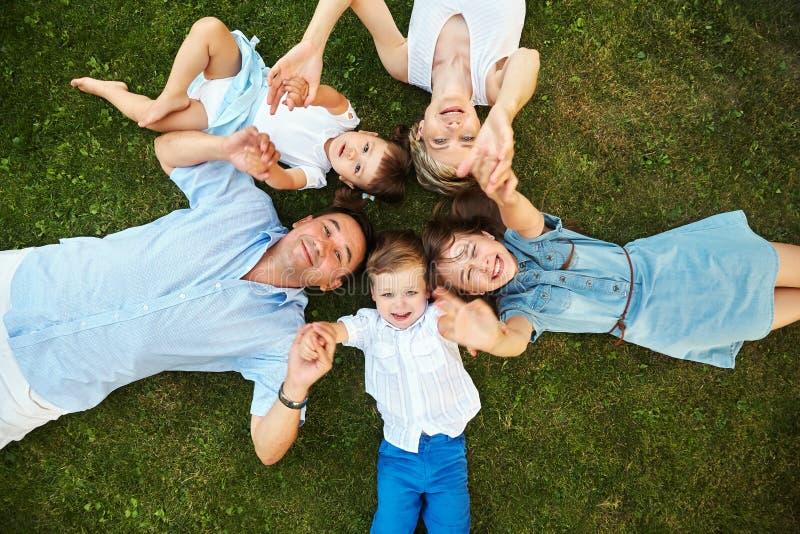 说谎在草的愉快的嬉戏的家庭户外 有孩子的父母在夏天 妈妈、爸爸和孩子 免版税库存图片