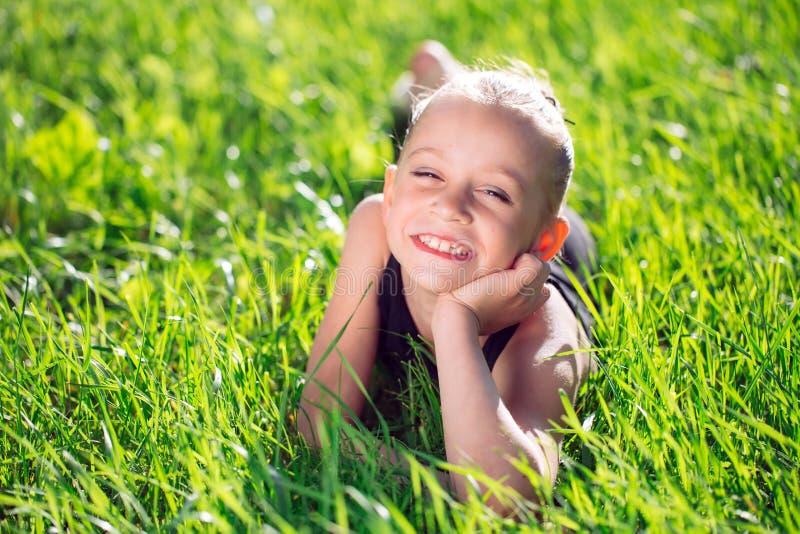 说谎在草的逗人喜爱的愉快的女孩 库存照片