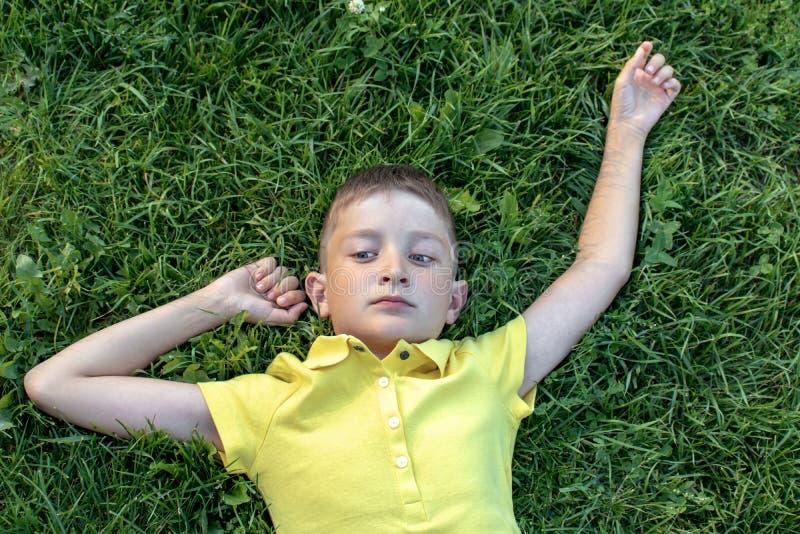 说谎在草的黄色衬衣的无忧无虑的白种人男孩 免版税库存照片