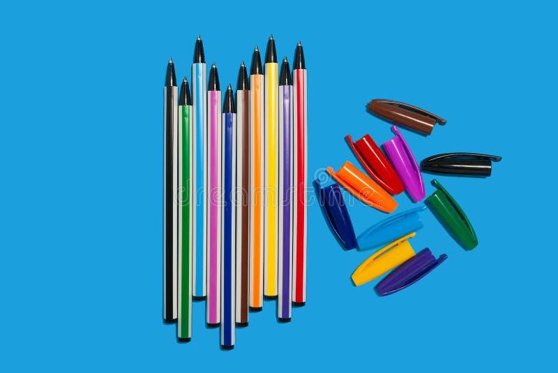说谎在蓝色背景的色的笔,不用盖帽 免版税库存图片