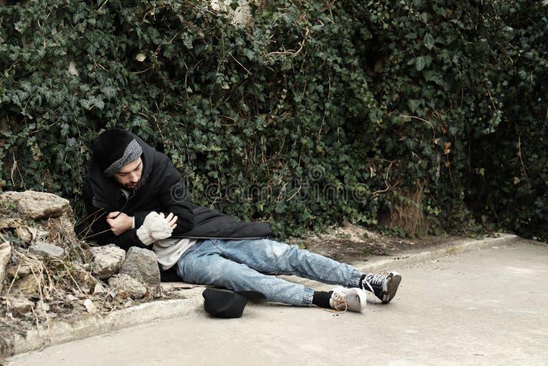 说谎在街道上的可怜的无家可归的人 库存照片