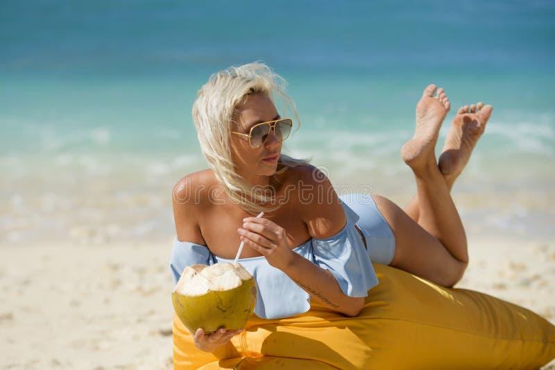 说谎在装豆子小布袋吊床的比基尼泳装的年轻可爱和轻松的白肤金发的妇女在热带天堂海滩饮用的椰子水 库存照片