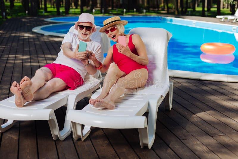 说谎在轻便折叠躺椅的现代领抚恤金者临近外部水池 免版税库存照片