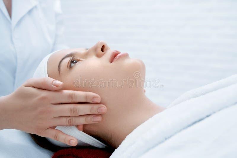 说谎在长沙发的客户,当女性美容师按摩时 库存照片