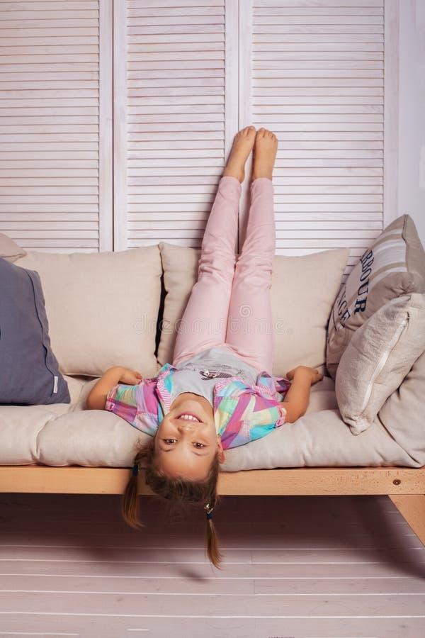 说谎在长沙发的小女孩颠倒 童年的概念 免版税库存照片