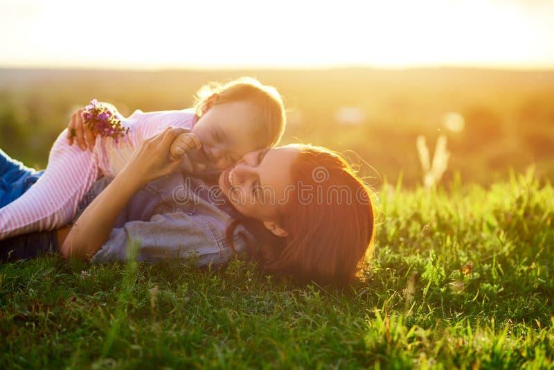 说谎在领域的草的母亲和女儿,当日落时 库存照片