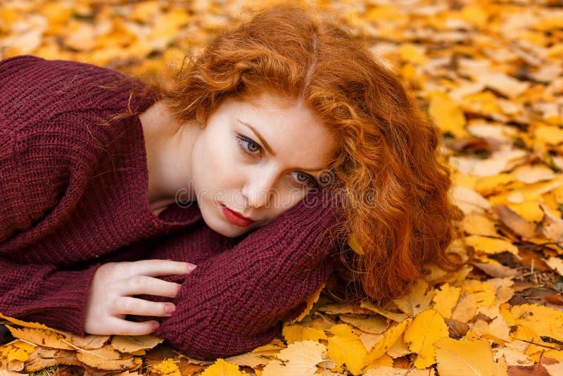 说谎在黄色叶子的逗人喜爱的红发女孩 免版税图库摄影