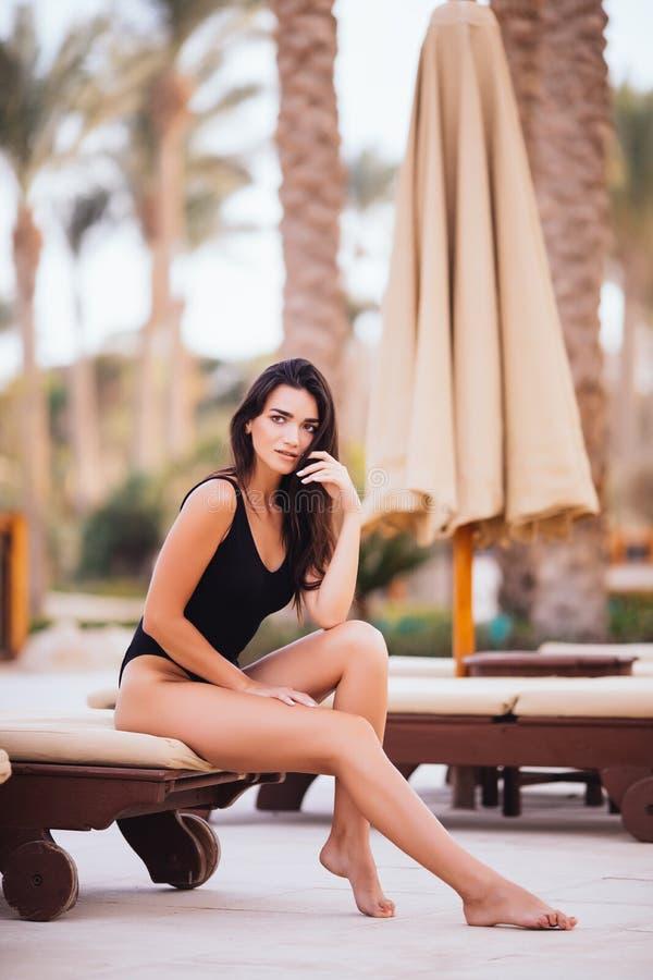 说谎在deckchair的美丽的妇女在海滩在棕榈下 库存照片