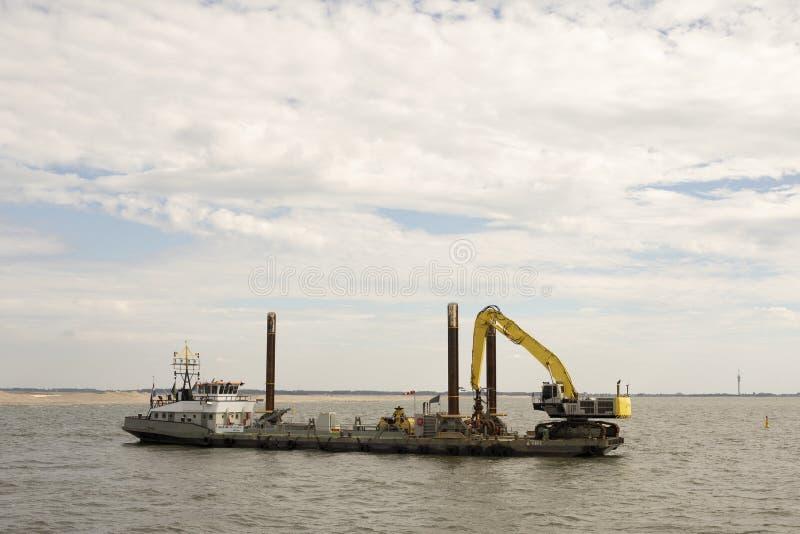 说谎在landwning的工地工作标志Wadden前面的Workboat 库存照片