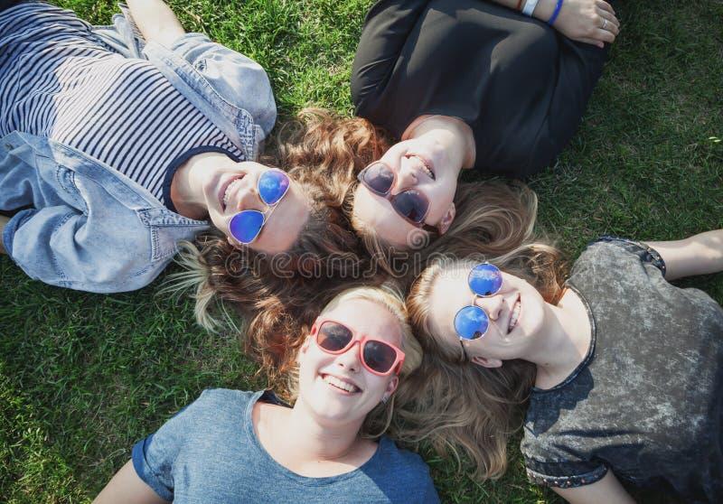 说谎在Th的小组愉快的微笑的无忧无虑的年轻时髦的女孩 免版税库存图片