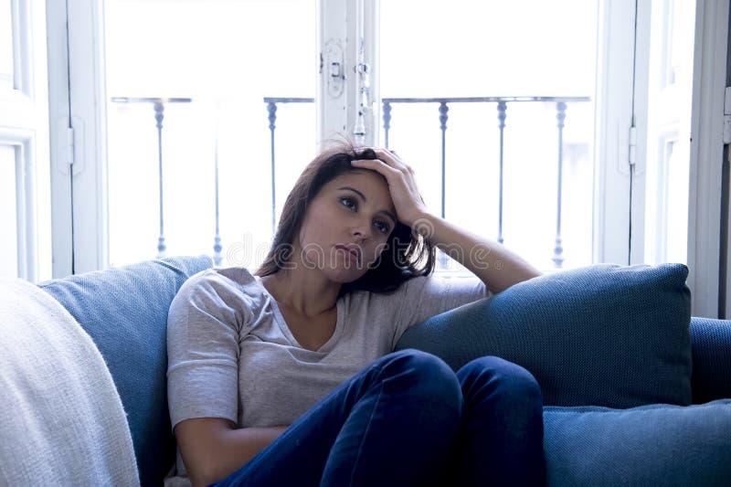 说谎年轻可爱的拉丁的妇女长沙发在家让感到遭受的消沉担心哀伤和绝望 图库摄影