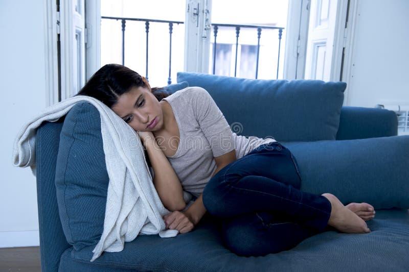 说谎年轻可爱的拉丁的妇女长沙发在家让感到遭受的消沉担心哀伤和绝望 免版税库存图片