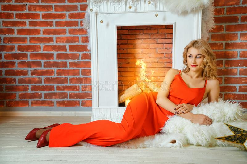 说谎由壁炉的红色礼服的美丽的年轻女人 免版税库存图片