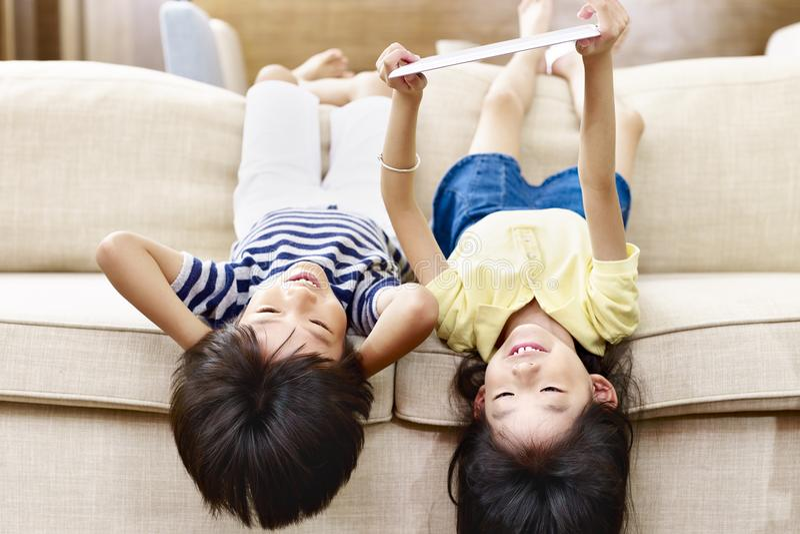 说谎颠倒在长沙发的两个亚裔小孩 库存照片