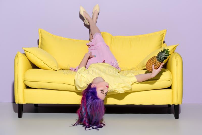 说谎颠倒在黄色长沙发的美丽的年轻女人 库存图片