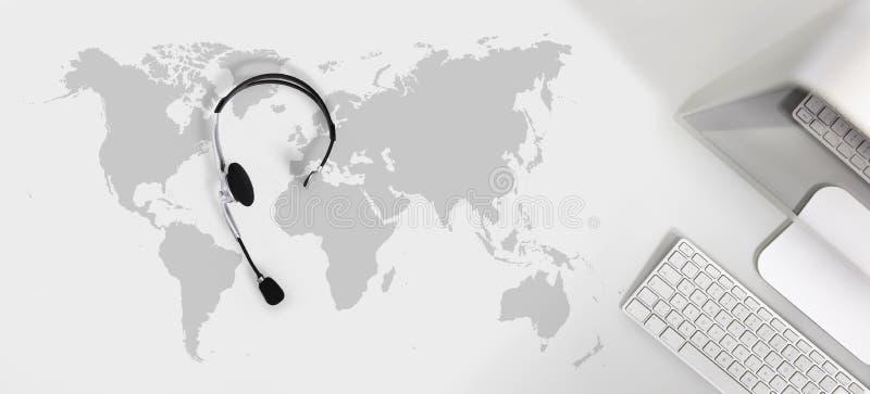 请与全球性概念,有耳机的的计算机顶视图书桌联系 库存图片