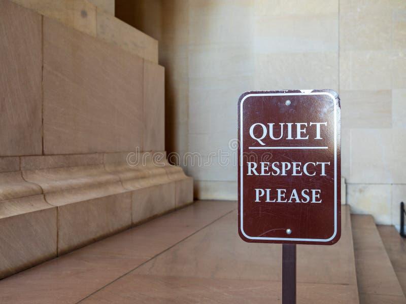 请使,尊敬在装饰显示前面的棕色标志平静 免版税库存照片