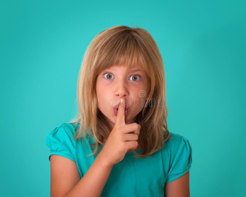 请做往照相机的孩子一个保持安静姿态 投入手指的美丽的小女孩由嘴唇决定和要求沈默 免版税库存照片