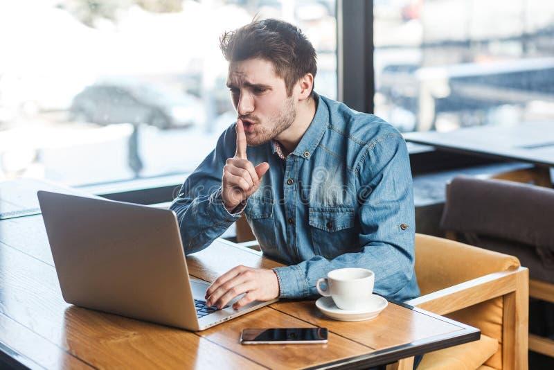 请是安静的!严重有胡子的年轻自由职业者侧视图画象蓝色牛仔裤衬衣的在咖啡馆坐并且做录影 库存图片