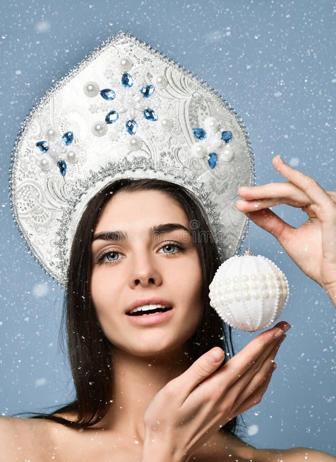 请求圣诞老人妇女 逗人喜爱的表面 健康皮肤 女孩在她的手上拿着一个圣诞树球 免版税库存图片